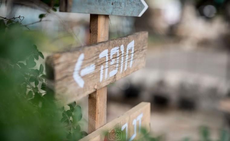 שלט עץ מיוחד מפנה לחתונה בכפר