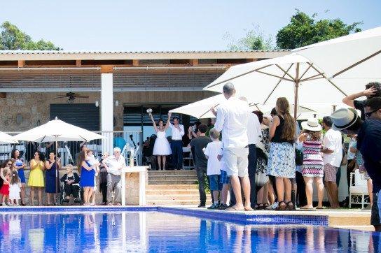 זוג מאושר יוצא מהוילה אל הבריכה רגע לאחר טקס החתונה